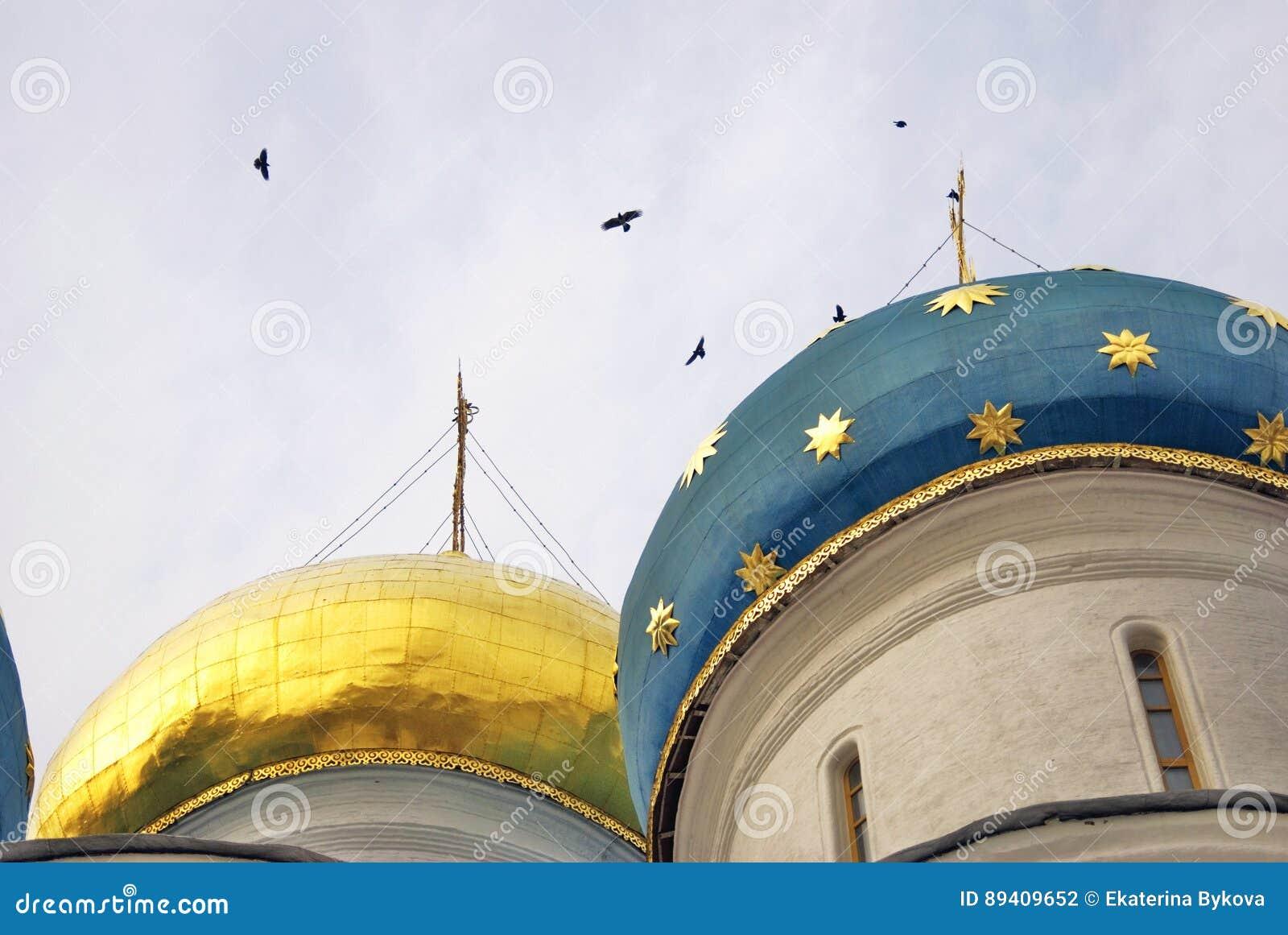 Igreja de Dormition da trindade Sergius Lavra Os pássaros voam em torno das cúpulas