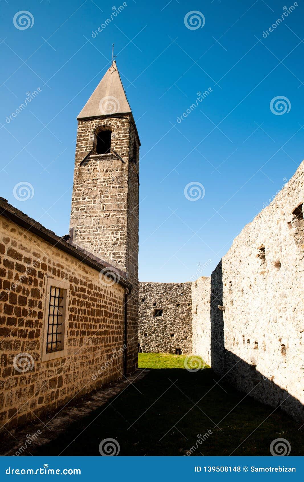 Igreja de trinity santamente e fortaleza medieval no sulco verde-oliva no Eslovênia a Europa Central de Hrastovlje