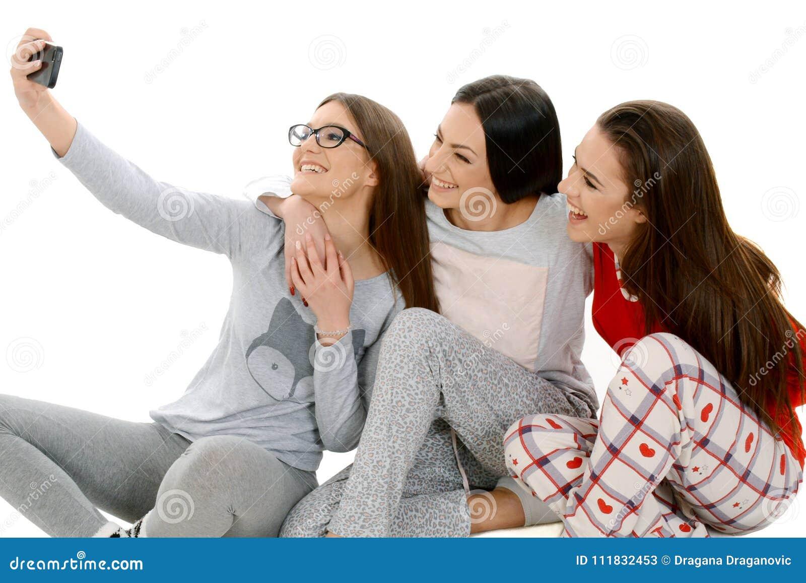 Ih feliz hermoso de tres muchachas sus pijamas que toman el selfie con