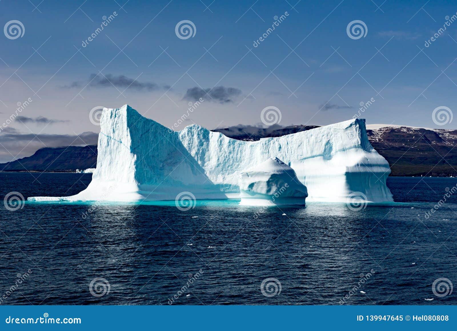 Ijsbergen voor Kust met sneeuw behandelde Bergen, Groenland De reusachtige Ijsbergbouw met toren