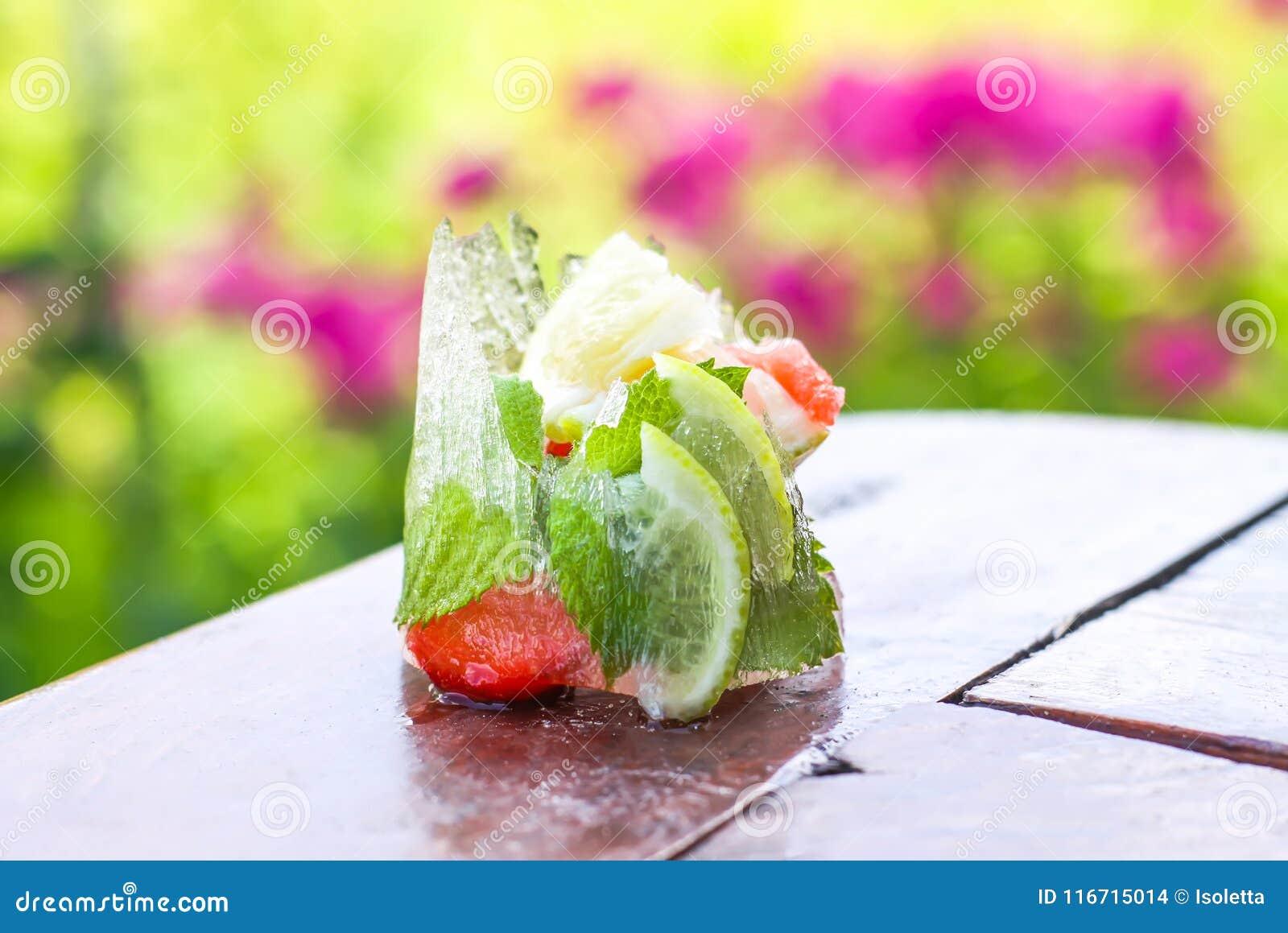 Ijsblokje met aardbei, citroen en verse groene muntbladeren op houten oppervlakte in openlucht