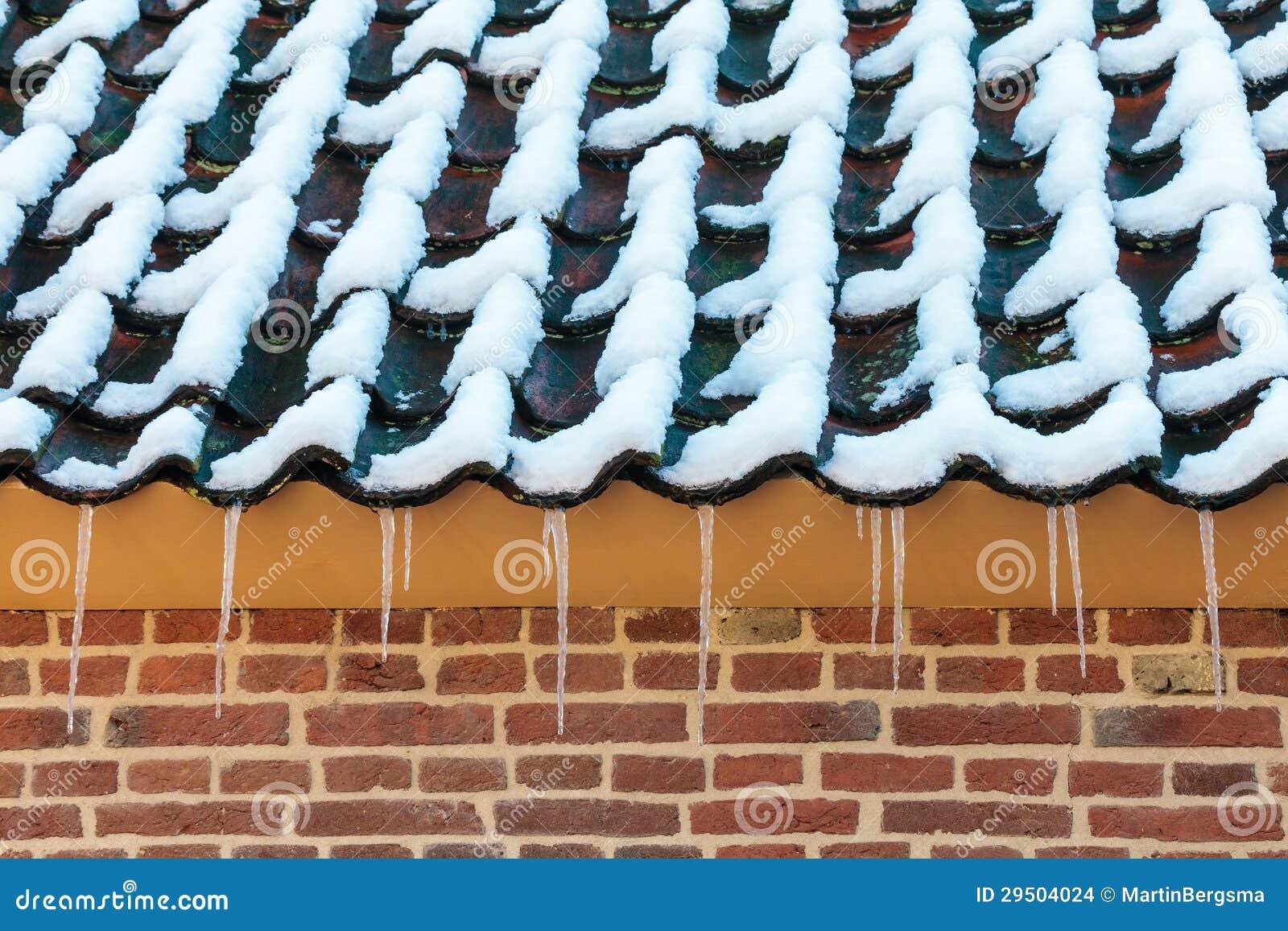 Ijskegels op het dak van een oud Nederlands landbouwbedrijf