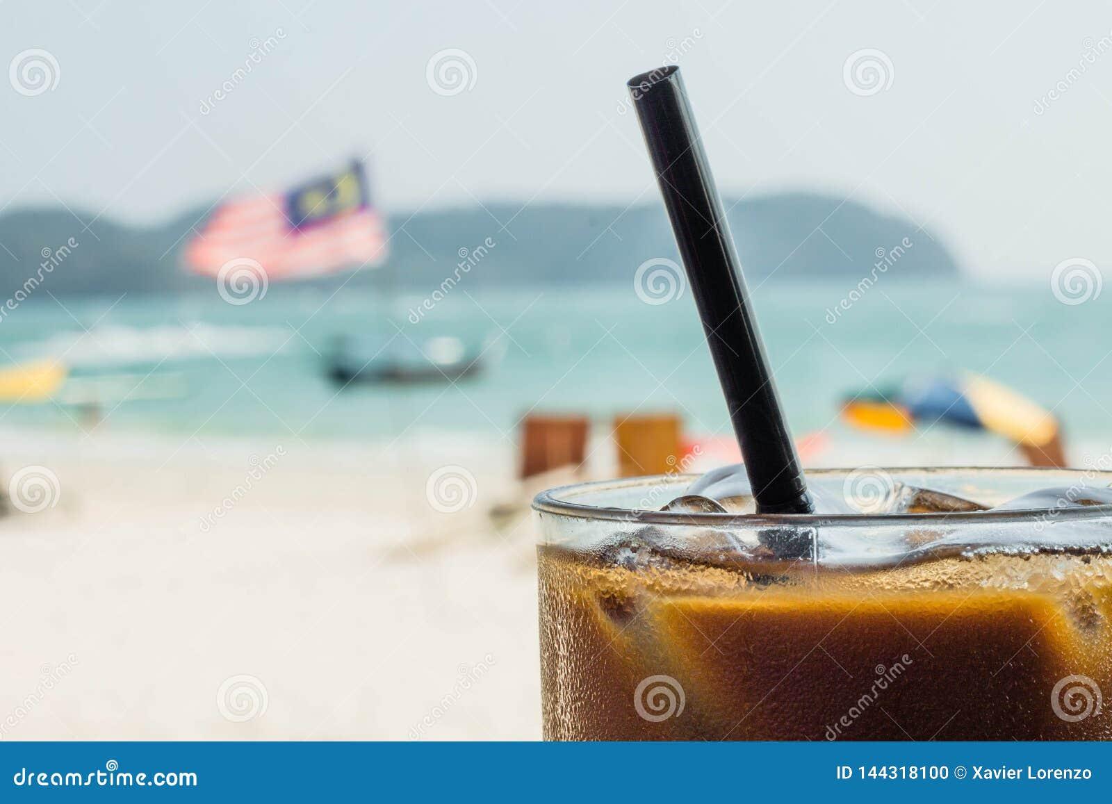 Ijskoffie met een Maleise vlag op de achtergrond Het genieten van vakantie van concept