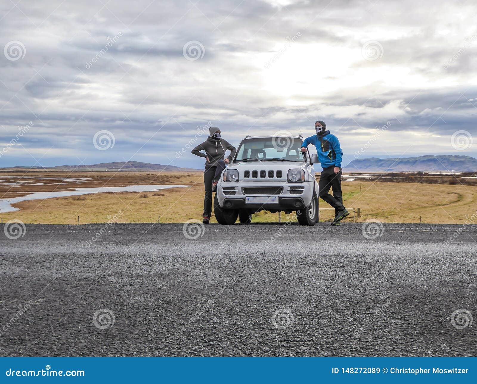 IJsland - een paar met de schilden die van het skeletgezicht zich voor een auto bevinden