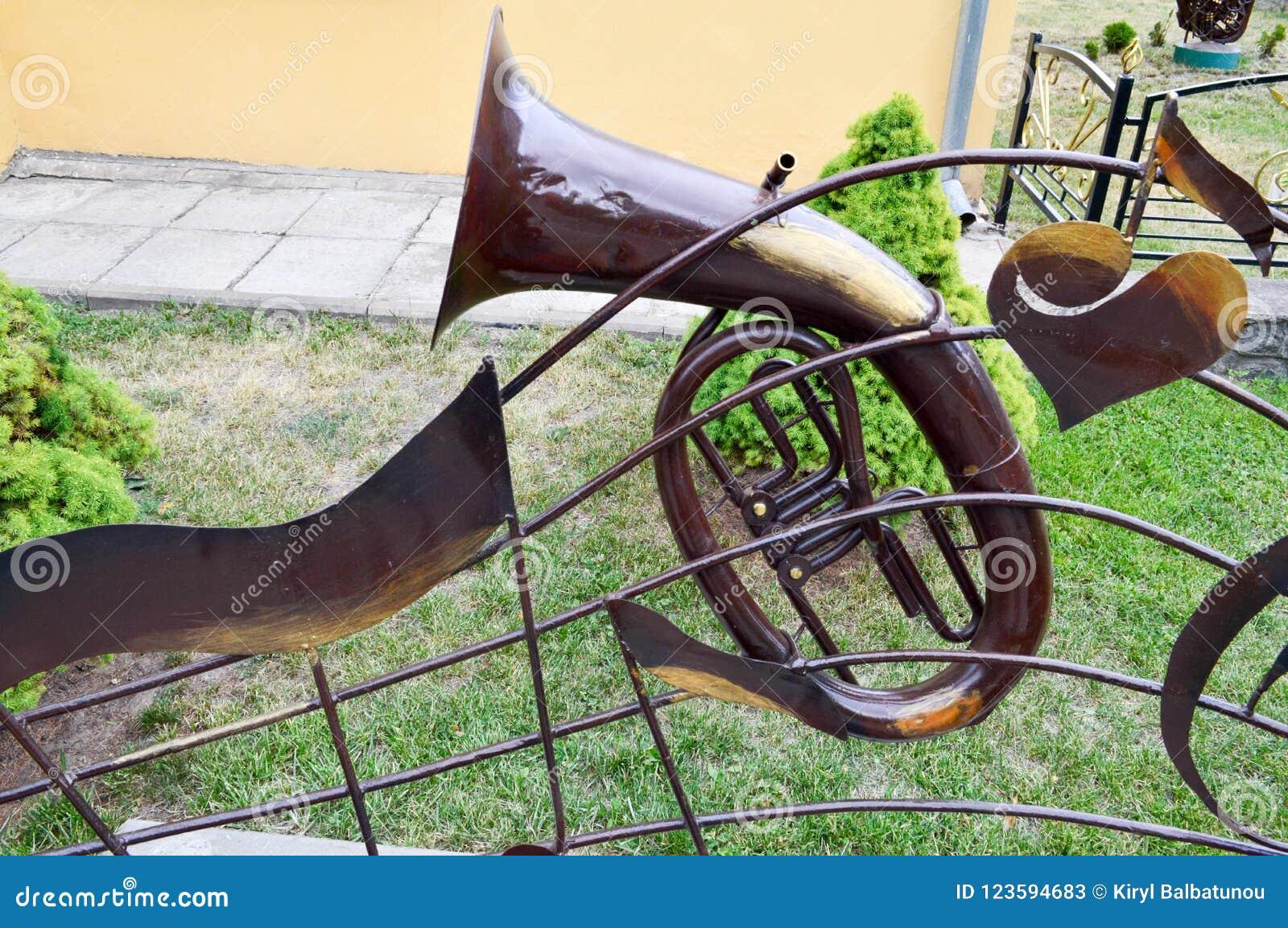 Ijzer bruine muzikale trompet, een pijp voor het spelen van muziek op een achtergrond van groen gras