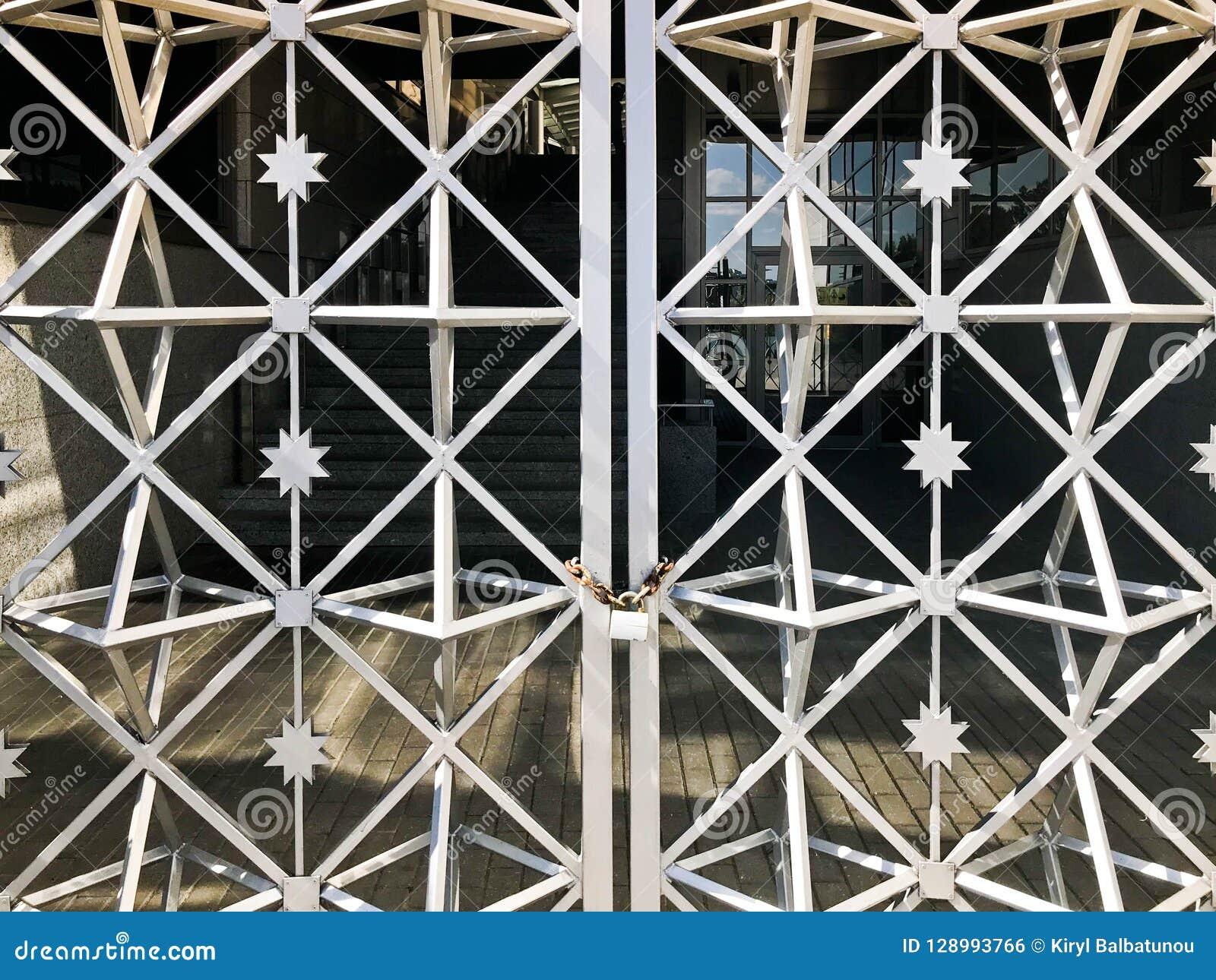 Ijzerpoorten, de omheining van de metaalbar op een sterke oude roestige ketting van verbindingen op een graanschuur groot slot da