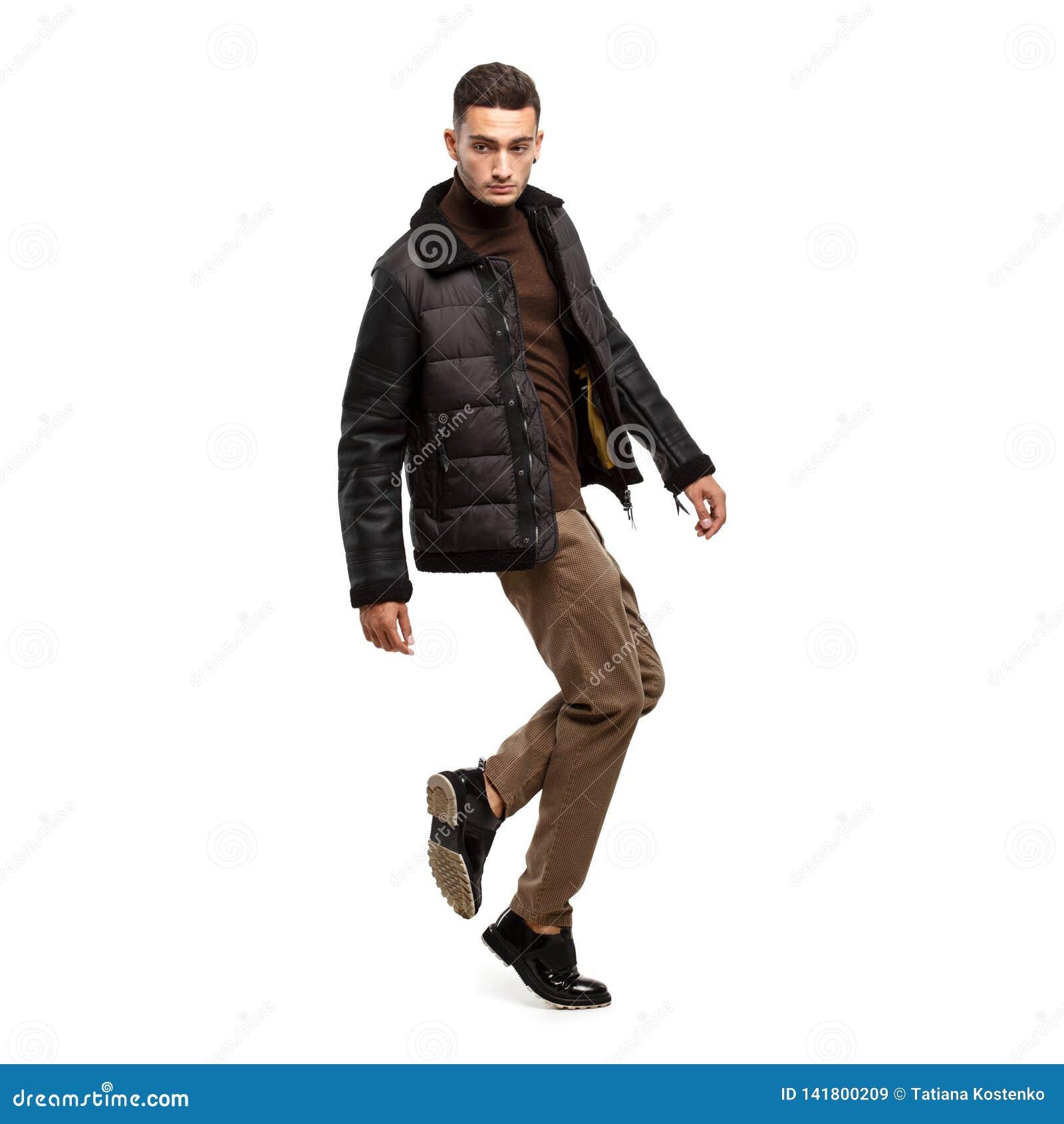 Iklädd brun halvpolokrage för ung stilfull man, flåsandeställningar och svart omslag på den vita bakgrunden i studion