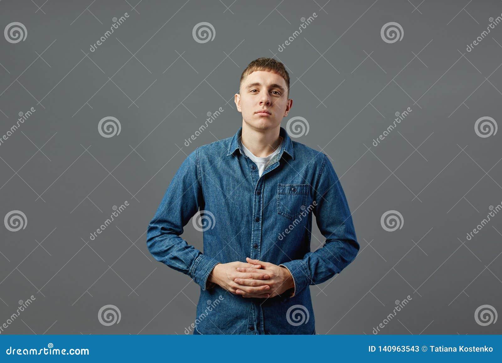 Iklädd grabb en vit t-skjorta, jeans och jeansskjorta som står med hans armar vikta i studion på den gråa bakgrunden