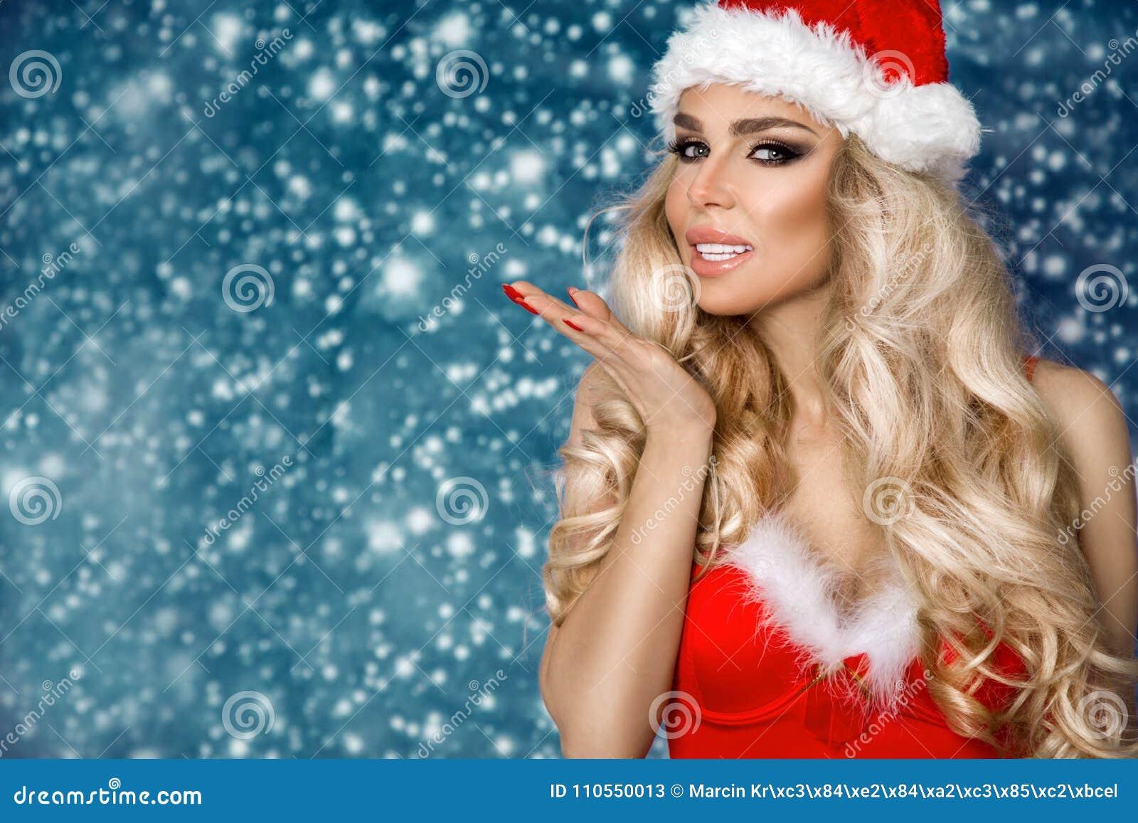 Iklädd härlig sexig blond kvinnlig modell en Santa Claus hatt och klänning