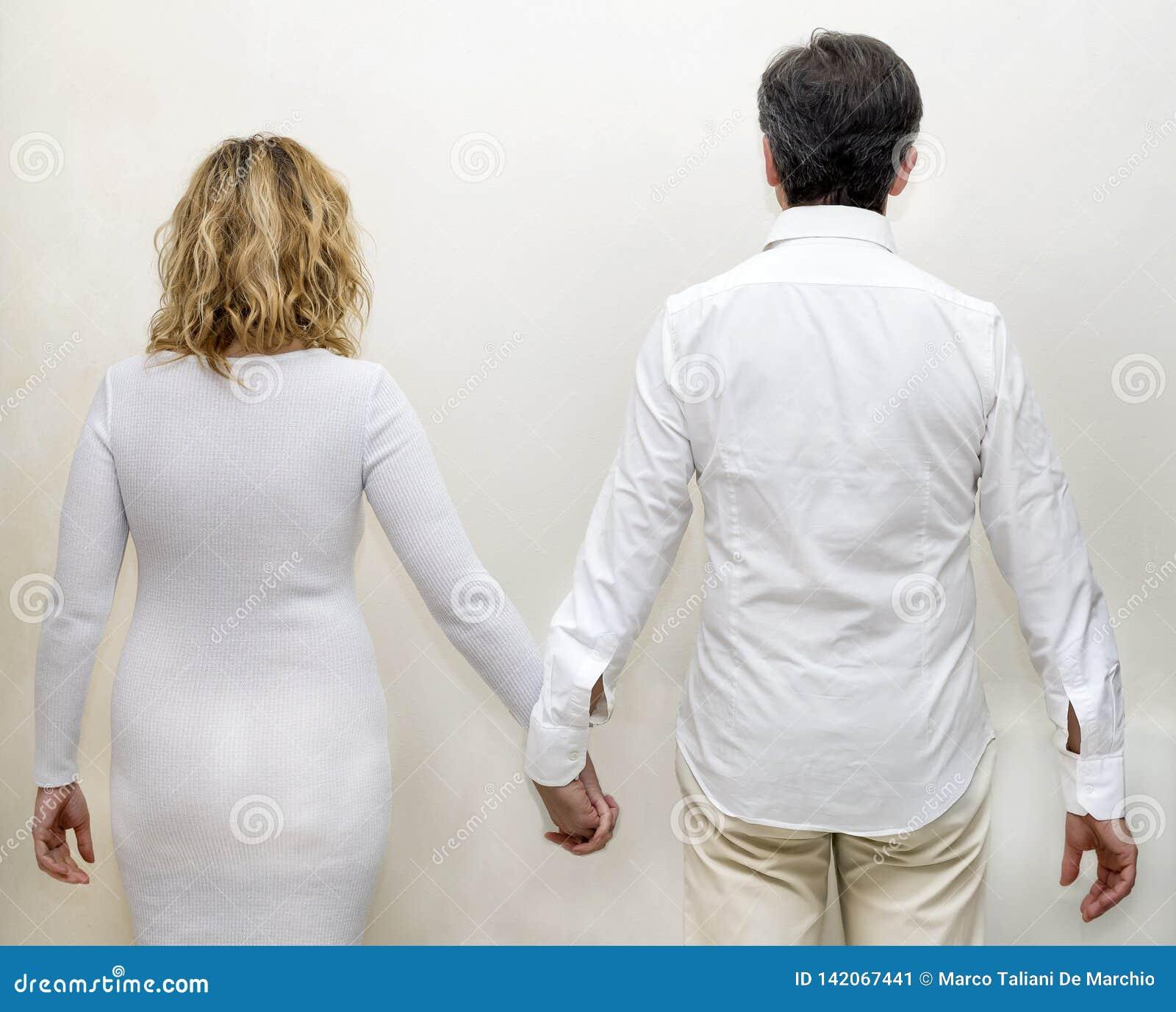 Iklädd vit för mogna par bakifrån som rymmer händer mot en vit bakgrund