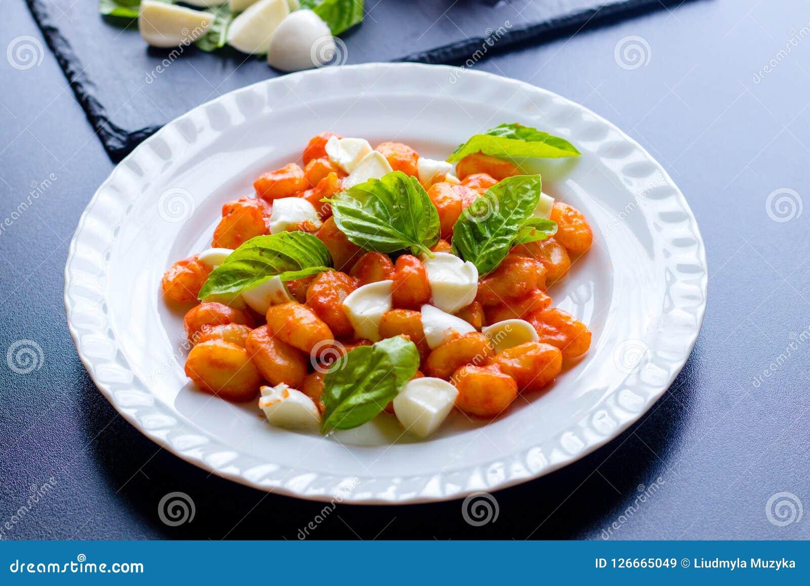 Il alla Sorrentina di gnocchi in salsa al pomodoro con le palle fresche verdi della mozzarella e del basilico è servito su un pia