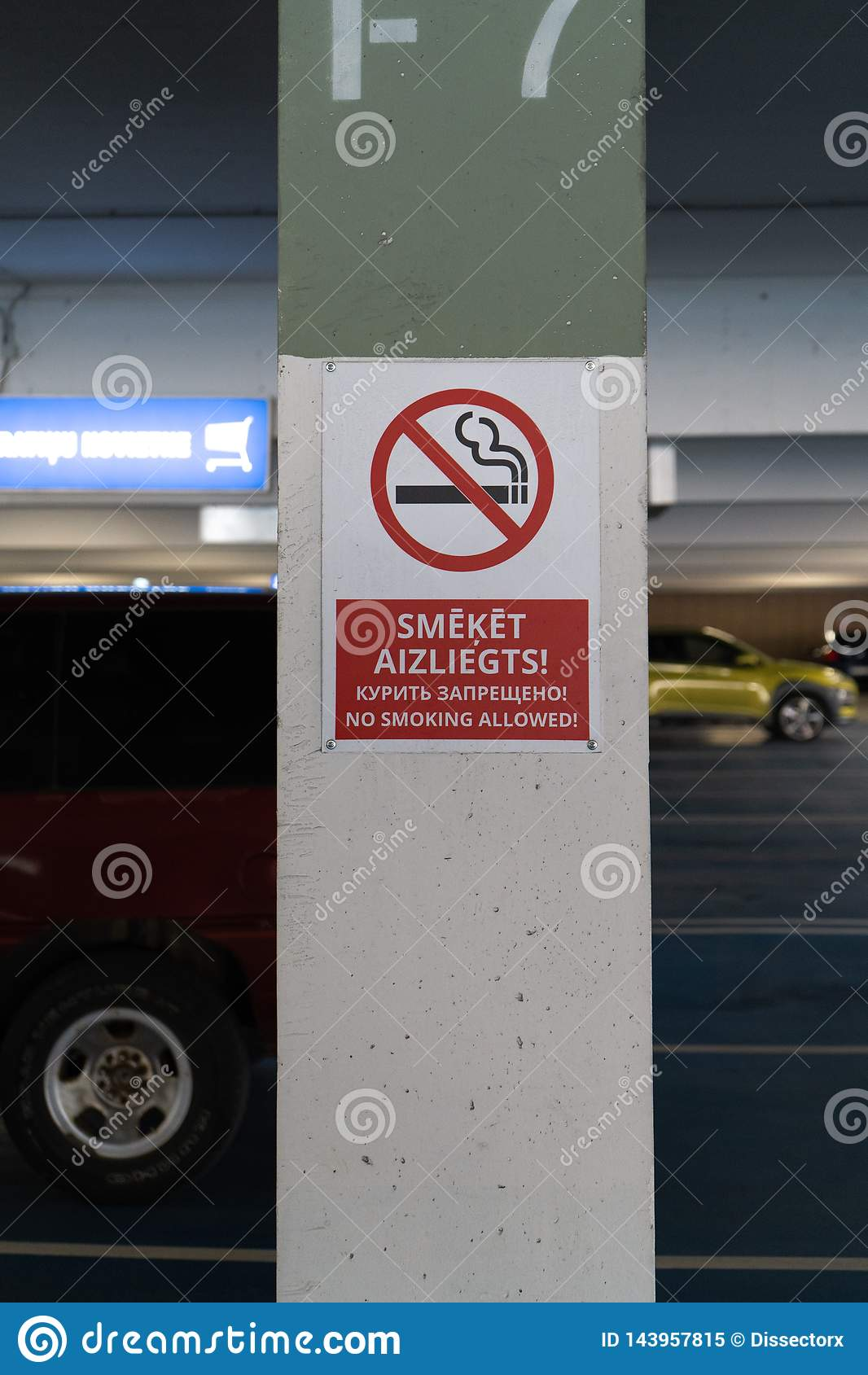 Il allower non fumatori rosso firma in tre lingue in un parcheggio sotterraneo con le automobili visibili nei precedenti