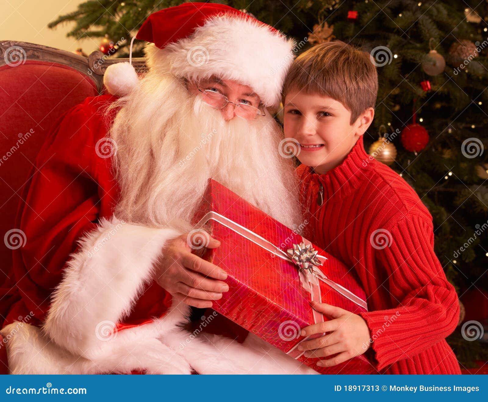 Il Babbo Natale che dà regalo al ragazzo davanti a Christm