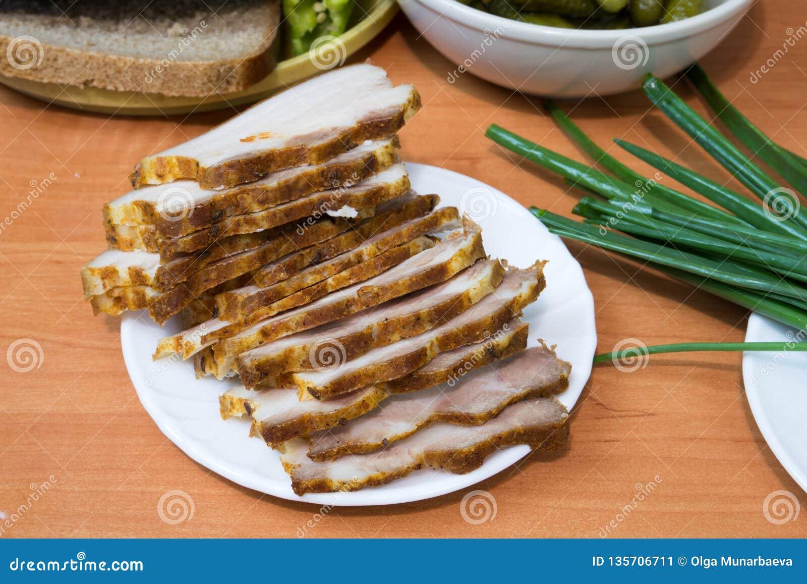 Il bacon inglese ha affettato su un piatto bianco