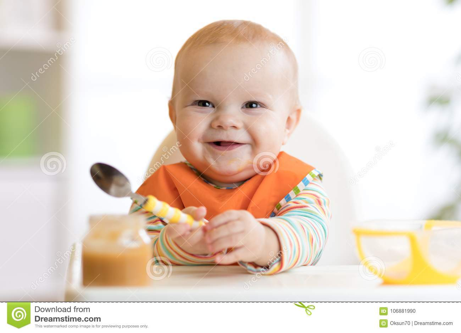 Il bambino allegro del bambino mangia l alimento stesso con il cucchiaio Ritratto del ragazzo felice del bambino nel seggiolone