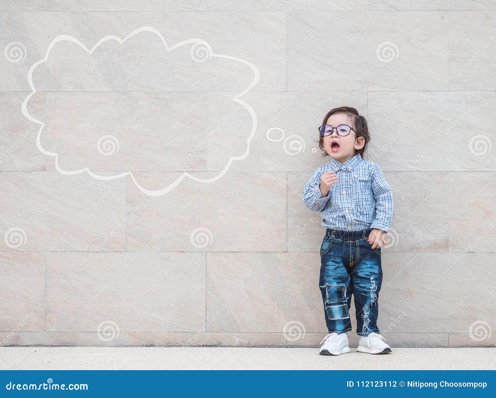 Il bambino asiatico del primo piano dice qualcosa azione con la casella di testo sul fondo strutturato di marmo della parete di p