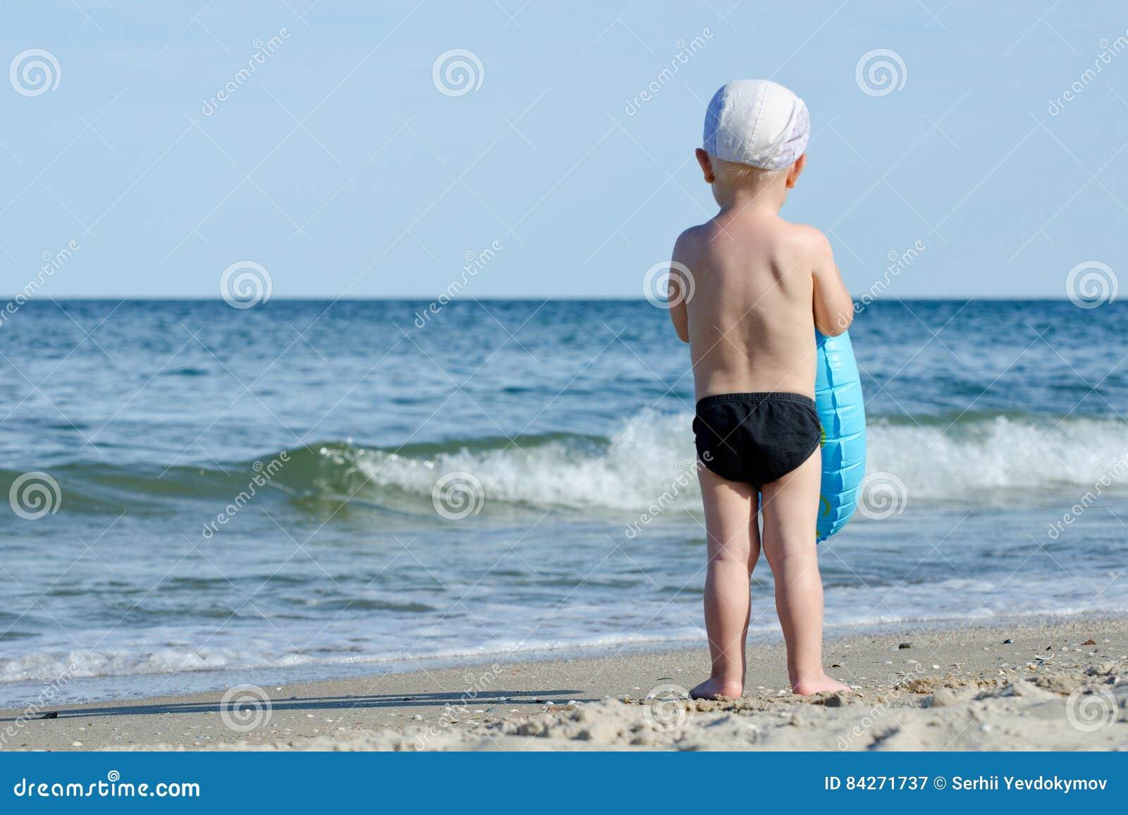 Costumi Da Bagno Per Bambino : Il bambino in costume da bagno ed in un cappuccio con un cerchio