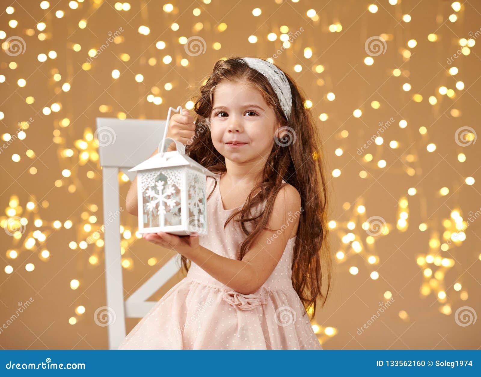 Il bambino della ragazza sta posando con la lanterna alle luci di natale, il fondo giallo, vestito rosa