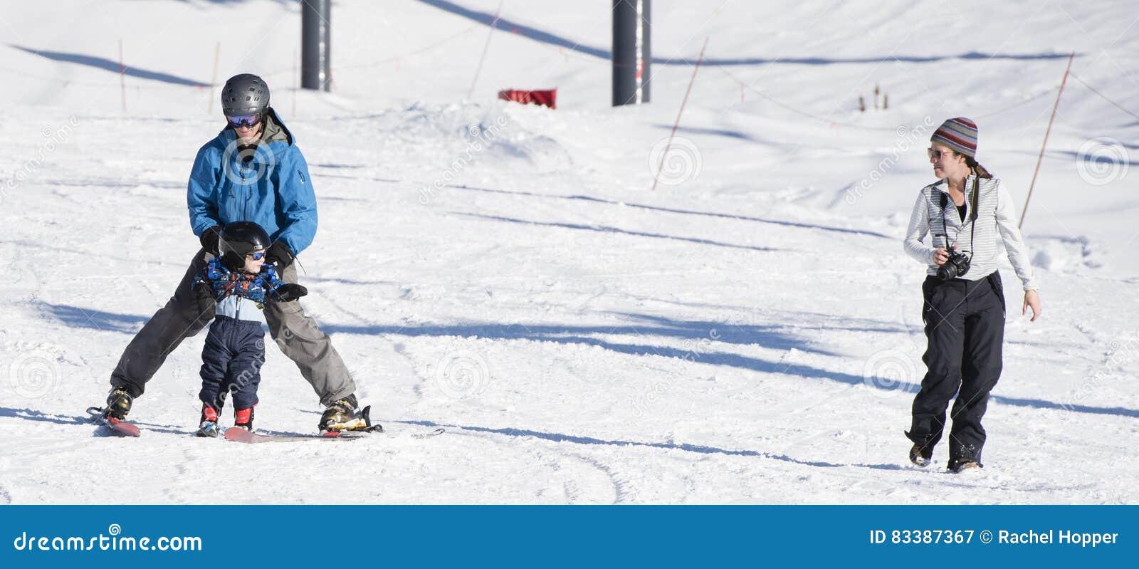 Il bambino impara sciare con il papà mentre gli orologi & la mamma prende le foto