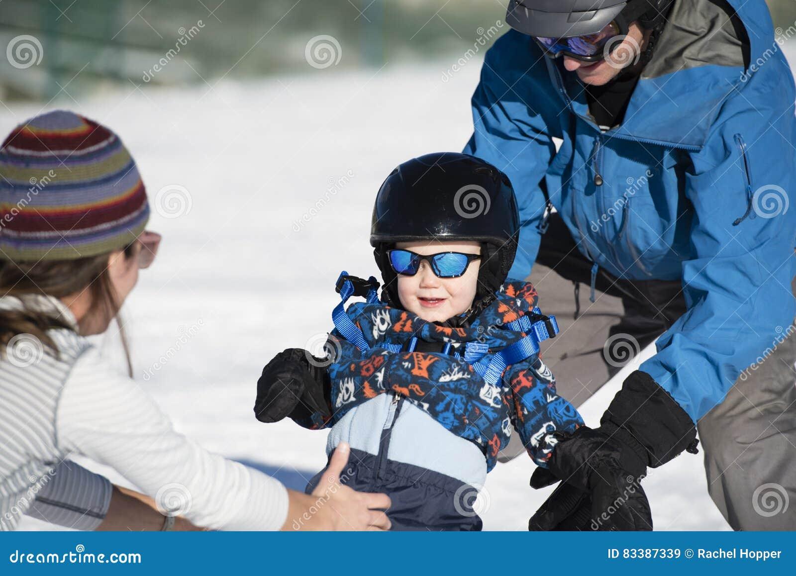 Il bambino impara sciare con il papà mentre orologi della mamma Vestito sicuro