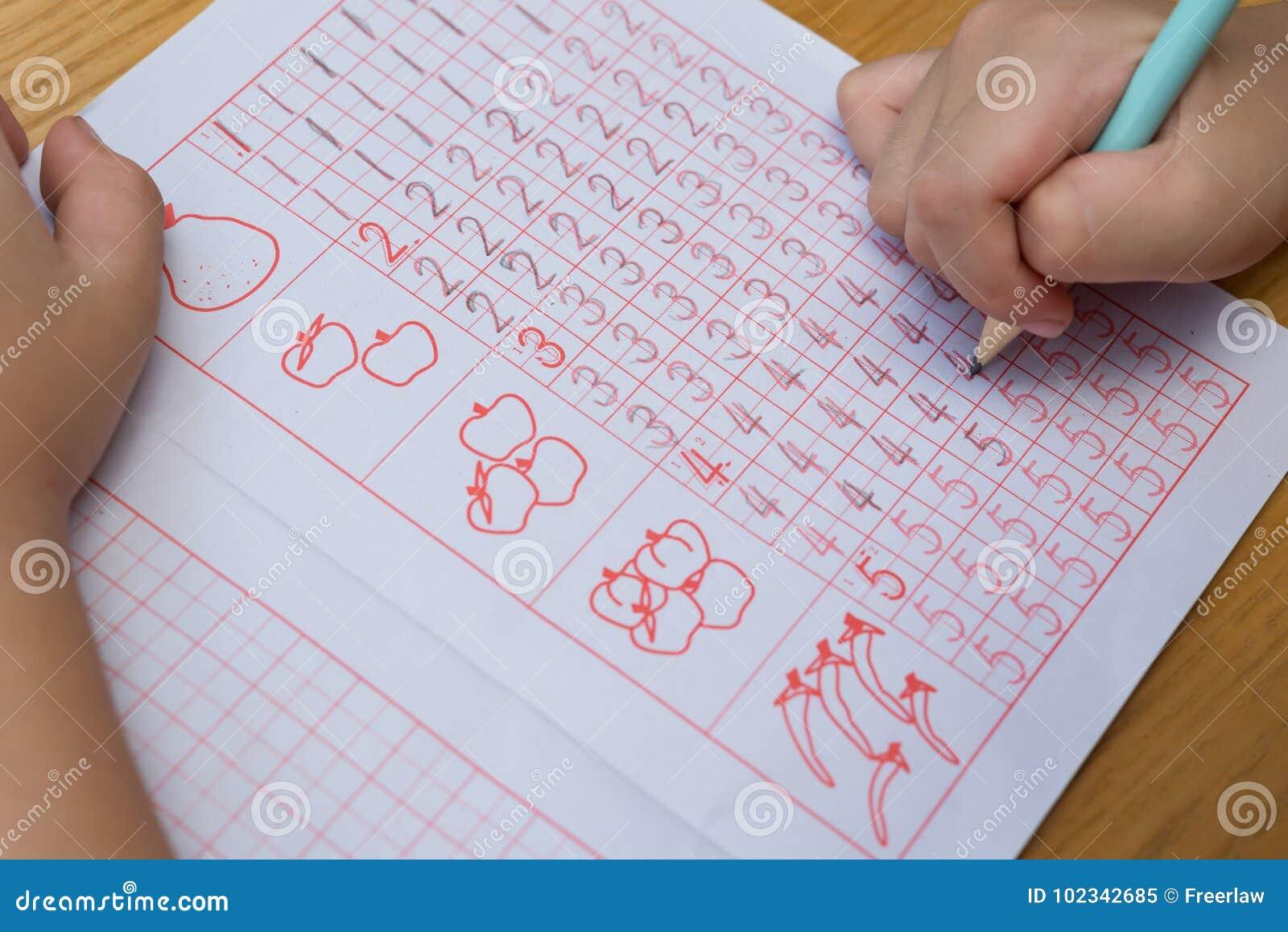 Il bambino impara scrivere i numeri arabi dalla seguente guida