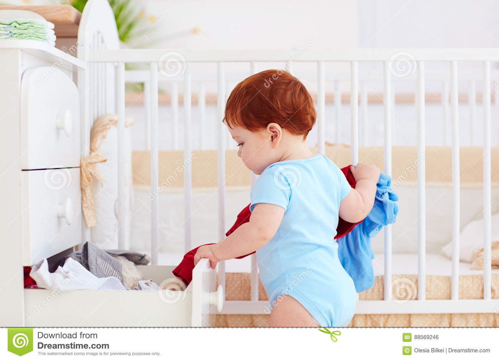 Il bambino infantile divertente che getta fuori copre dall apprettatrice a casa