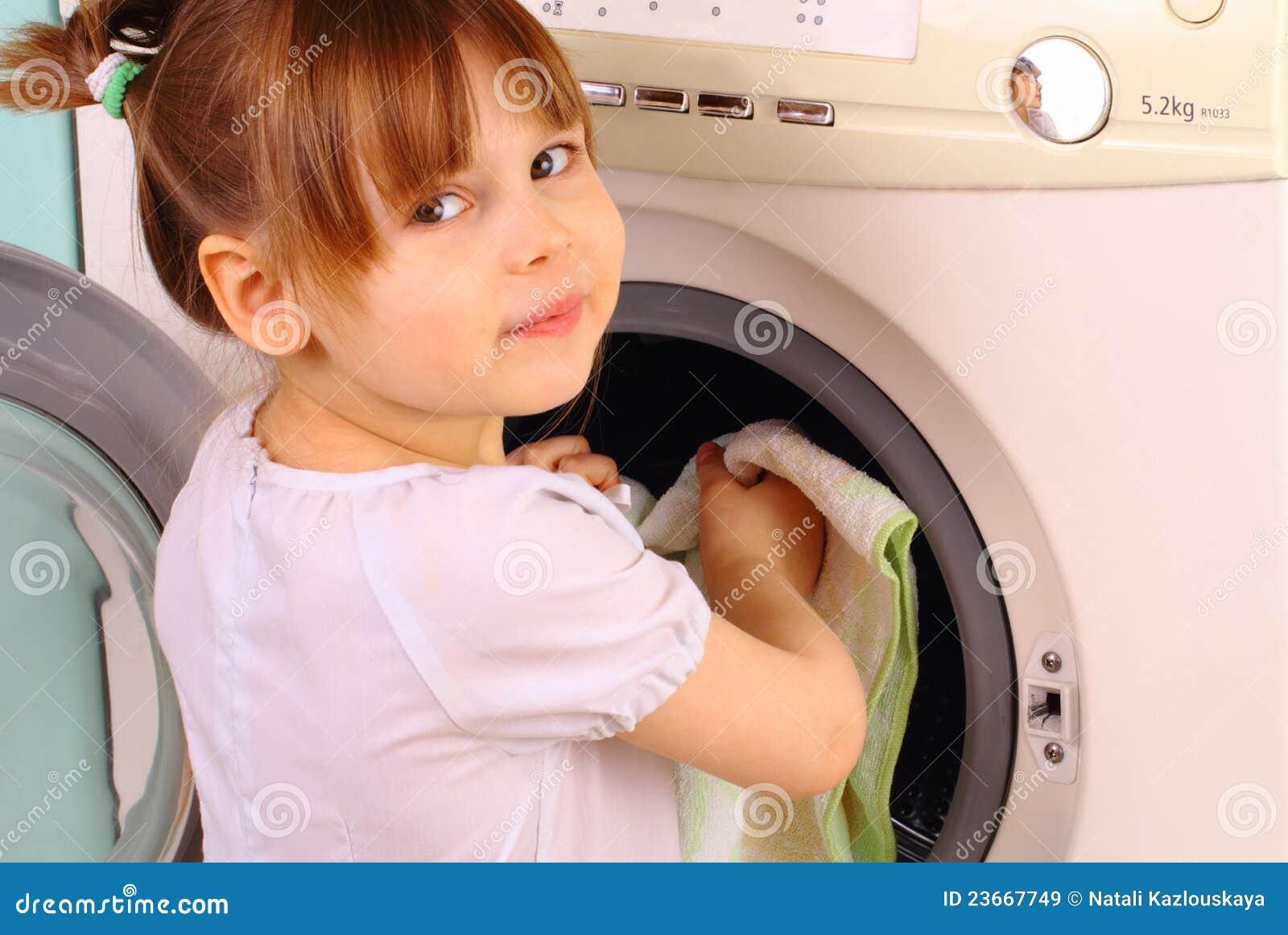 Il bambino mette i tovaglioli nella lavatrice