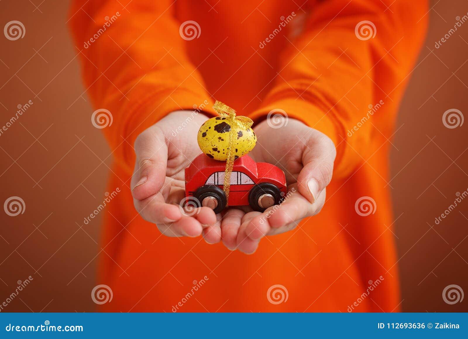 Il bambino passa la tenuta dell uovo di Pasqua sull automobile su fondo arancio Concetto di festa