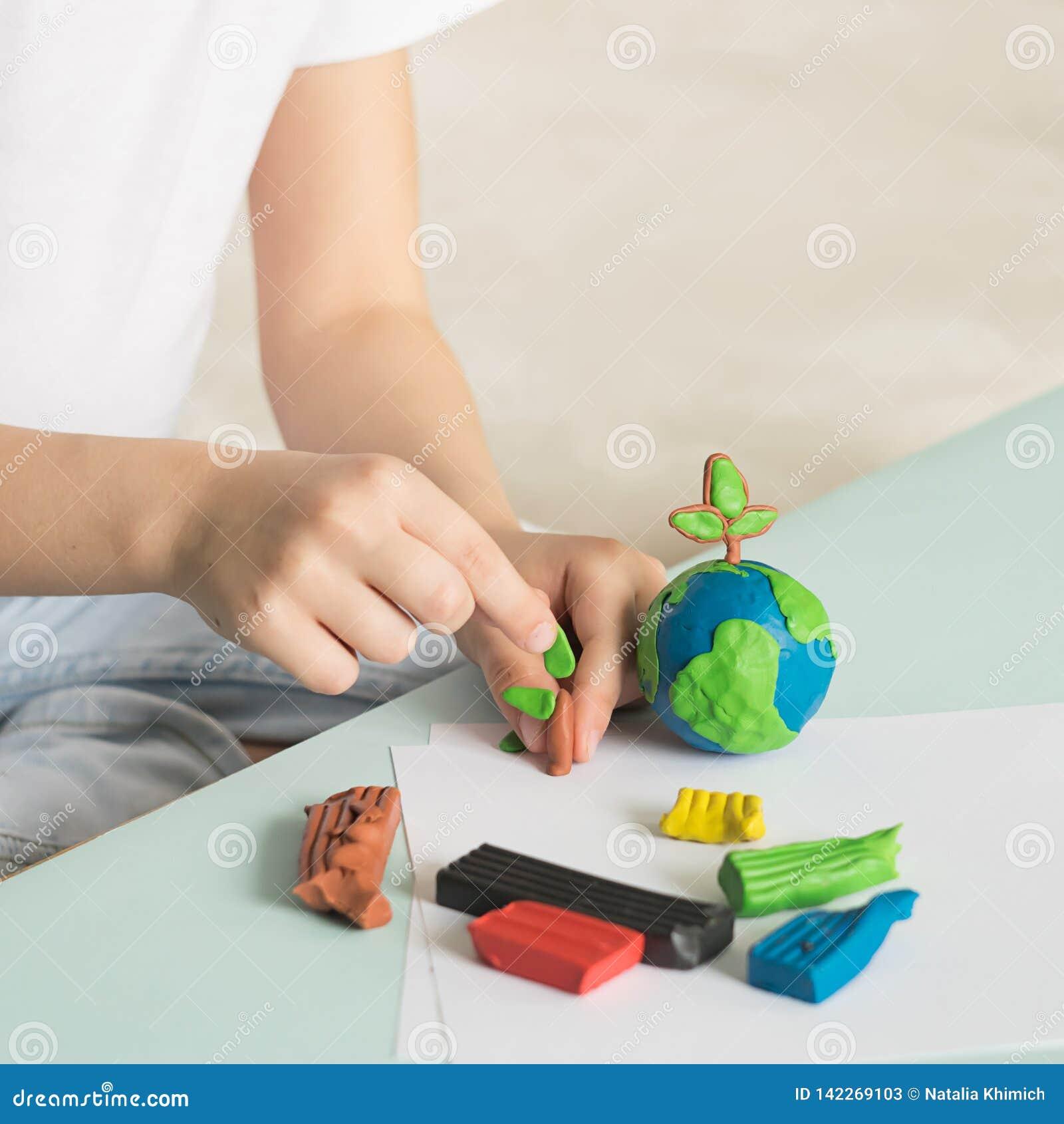 Il bambino scolpisce da plasticine il globo e gli alberi La posizione del pianeta in palme dei bambini Concetto di ecologia