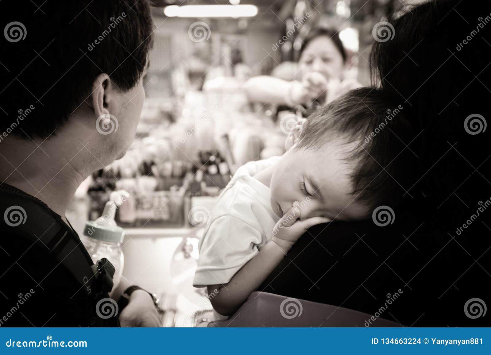 Il bambino stanco ritiene stanco e dorme sulla spalla di sua madre