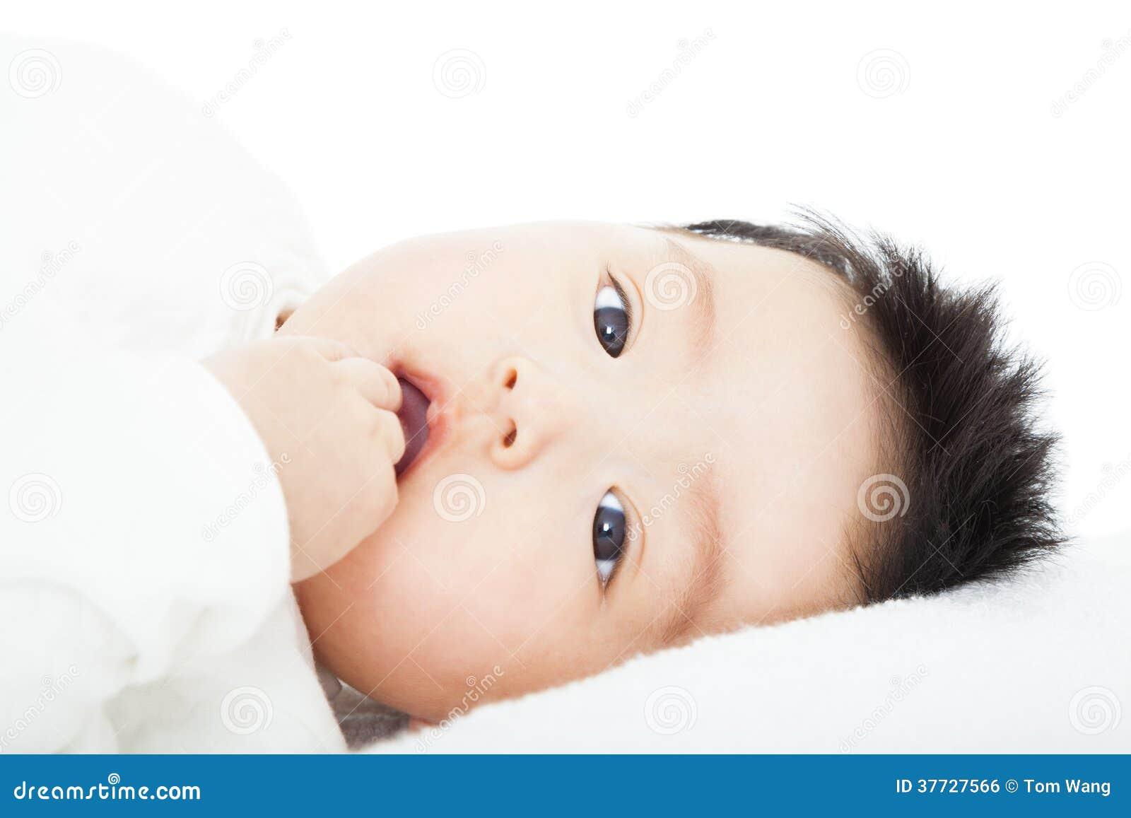 Il bambino sveglio succhia il suo pollice che si trova a letto immagine stock libera da diritti - Letto che si chiude ...