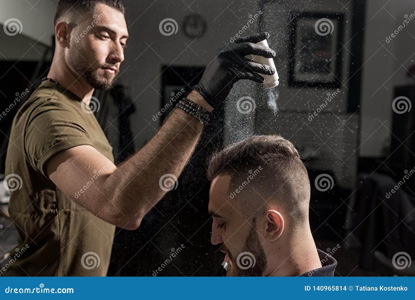 Il barbiere bello sta riparando la designazione del giovane brutale con uno styler asciutto ad un parrucchiere
