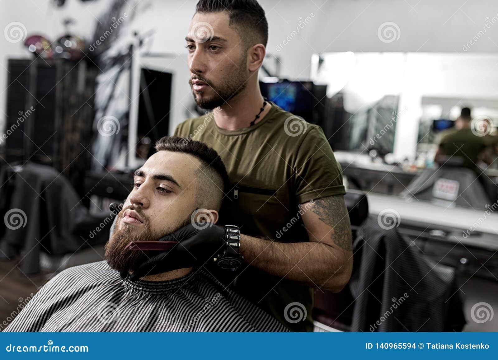 Il barbiere bello tiene le sue mani sulla barba di giovane uomo brutale e degli sguardi allo specchio ad un parrucchiere
