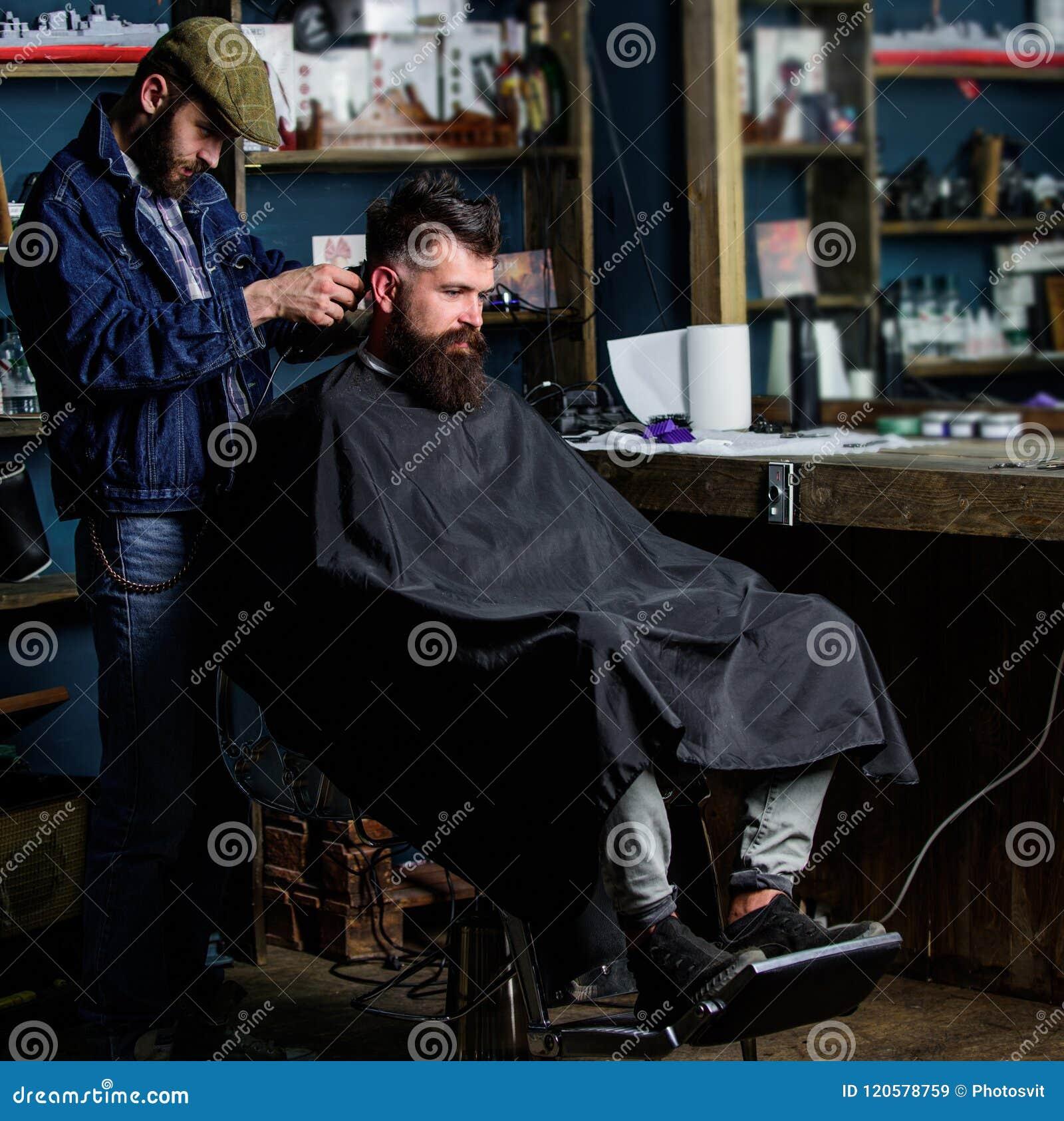 Il barbiere con la tosatrice lavora a taglio di capelli del fondo barbuto del parrucchiere del tipo Cliente dei pantaloni a vita