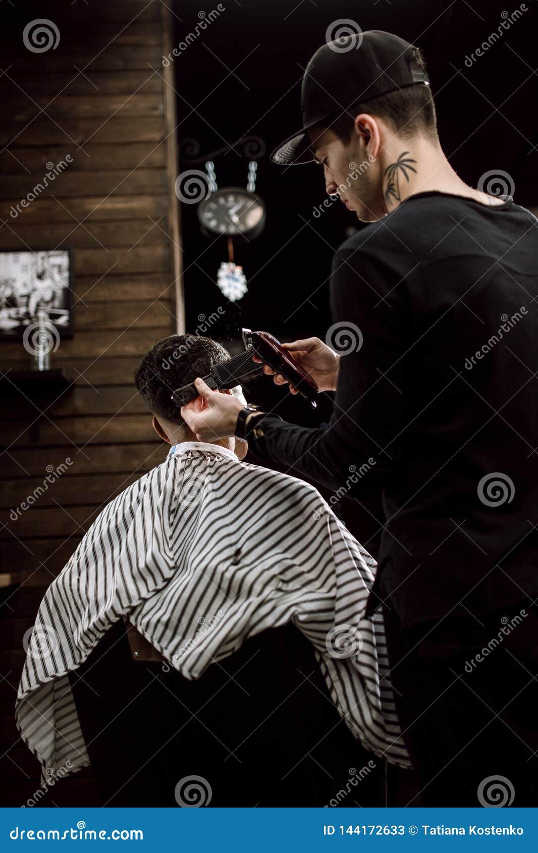 Il barbiere di modo fa i capelli del taglio di rasoio per un uomo moro alla moda in un parrucchiere alla moda