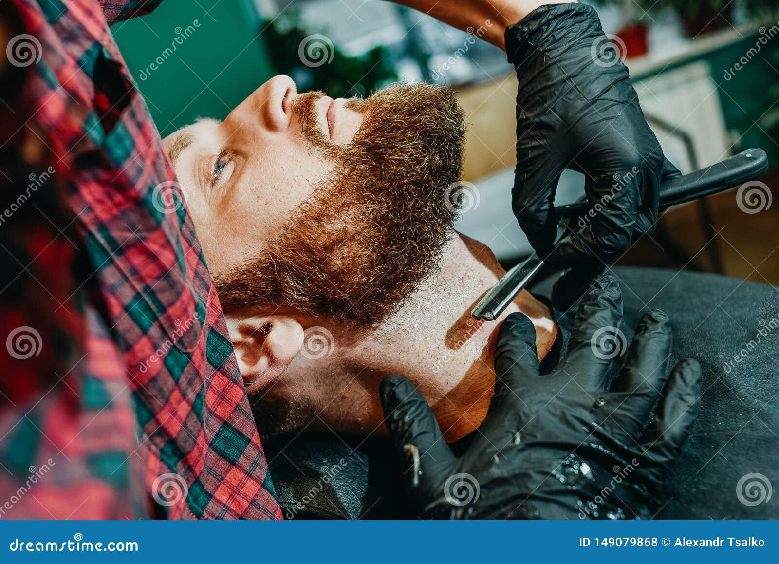 Il barbiere rade la sua barba con un uomo con un rasoio