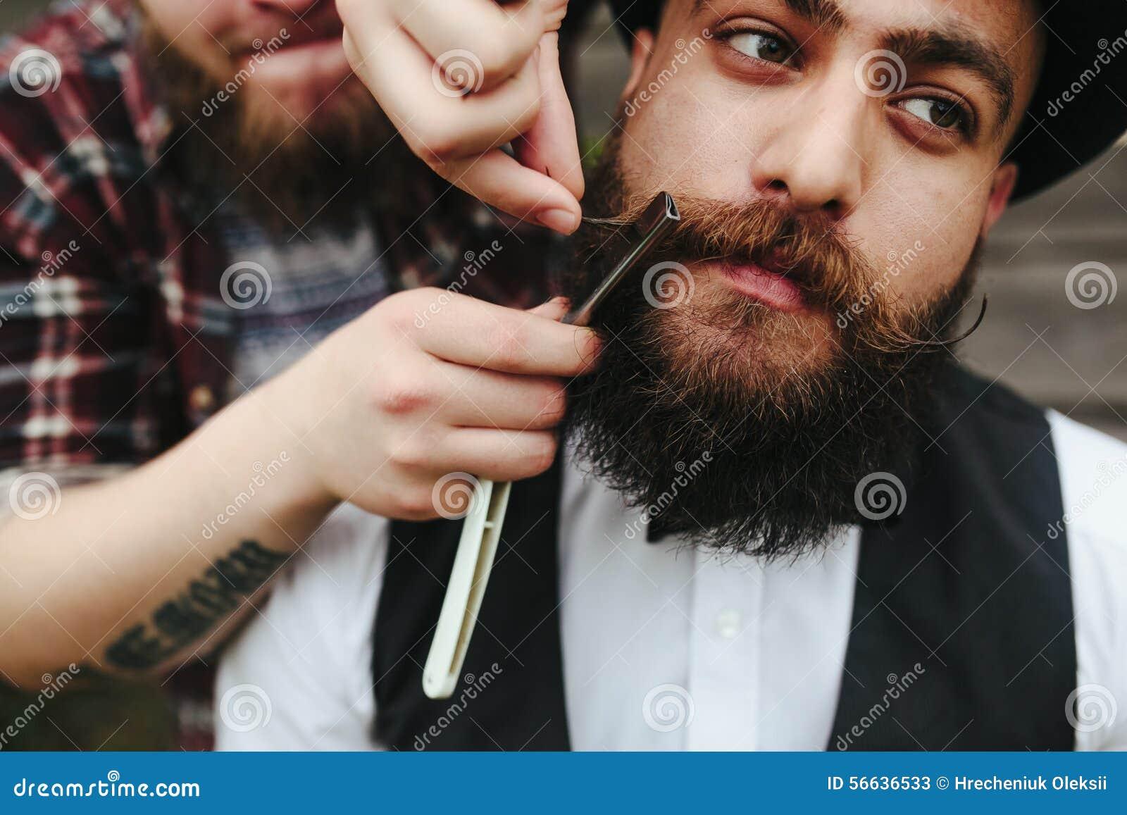 Il barbiere rade un uomo barbuto