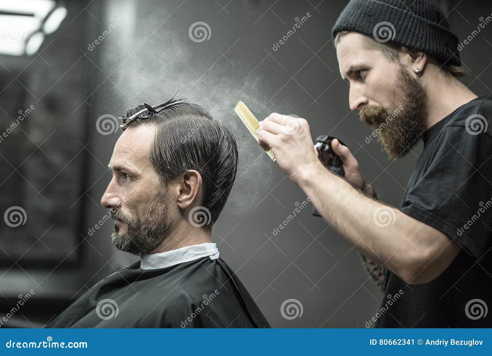 Il barbiere sta utilizzando la bottiglia dello spruzzo