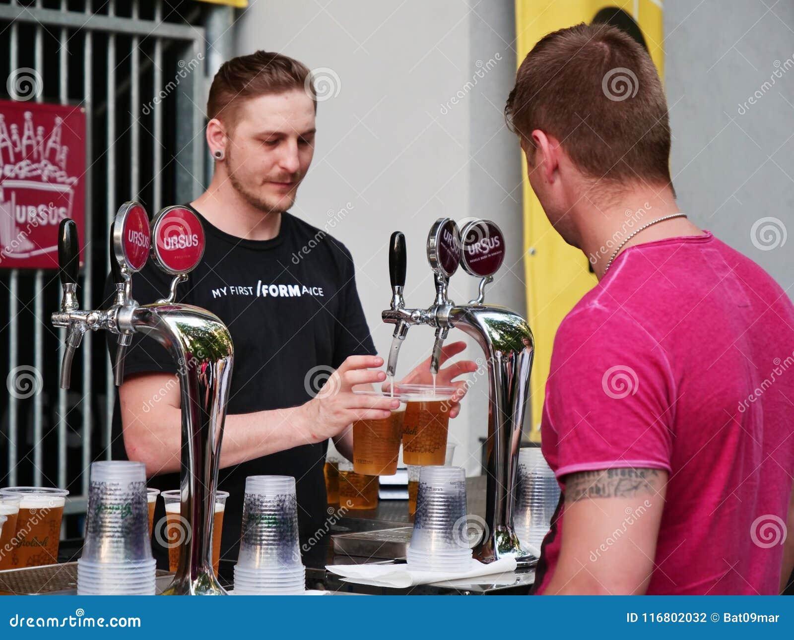 Il barista versa la birra dal rubinetto dietro il contatore