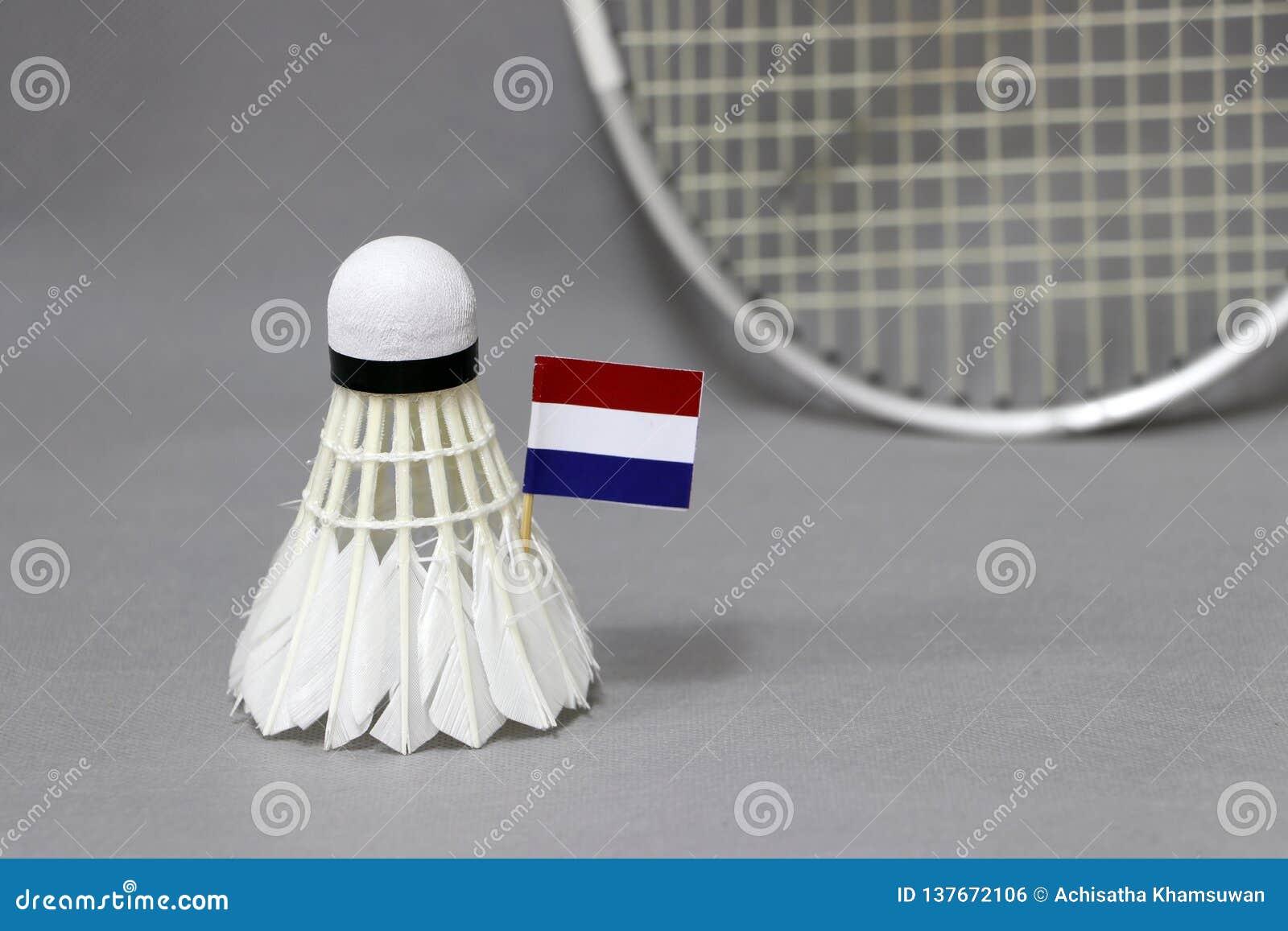 Il bastone della bandiera di Mini Netherlands sul volano bianco sui precedenti grigi e fuori mette a fuoco la racchetta di volano