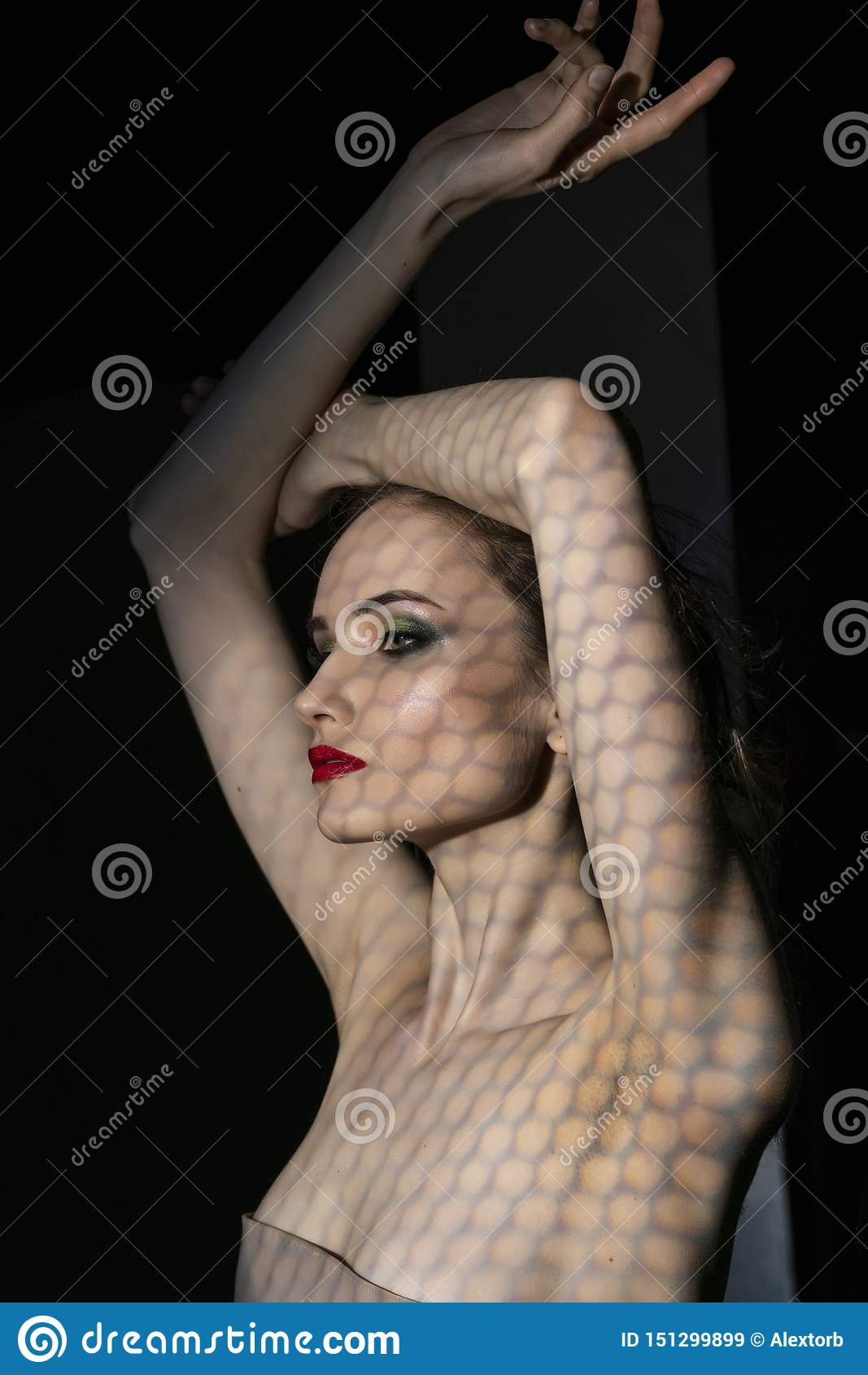 Il bello modello della ragazza con le labbra rosse compone e spalle nude coperte di maschera sotto forma di rete di esagonale