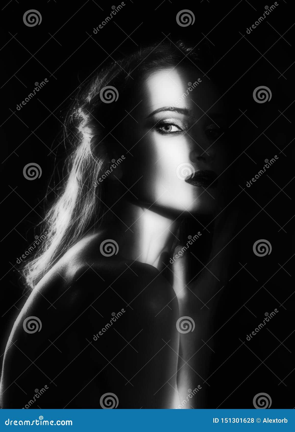 Il bello modello della ragazza con le labbra rosse compone e spalle nude nella tonalità, con una siluetta accesa e una striscia d