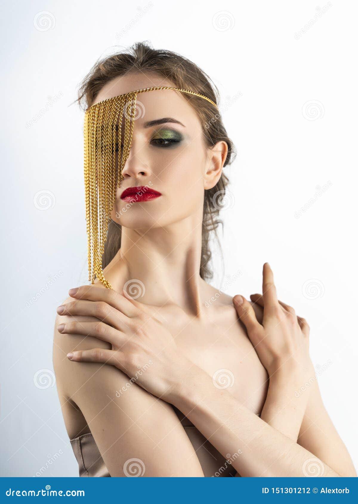 Il bello modello della ragazza con le labbra rosse prepara e spalle nude che indossano i gioielli concettuali di modo fatti delle
