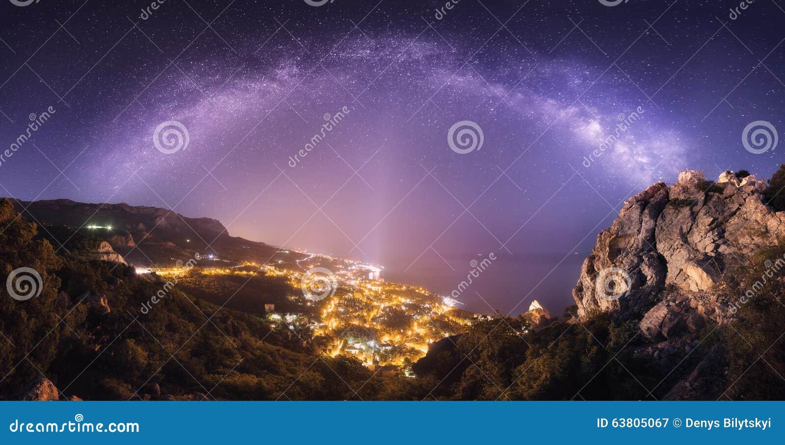 Il bello paesaggio di notte con la Via Lattea contro la città si accende