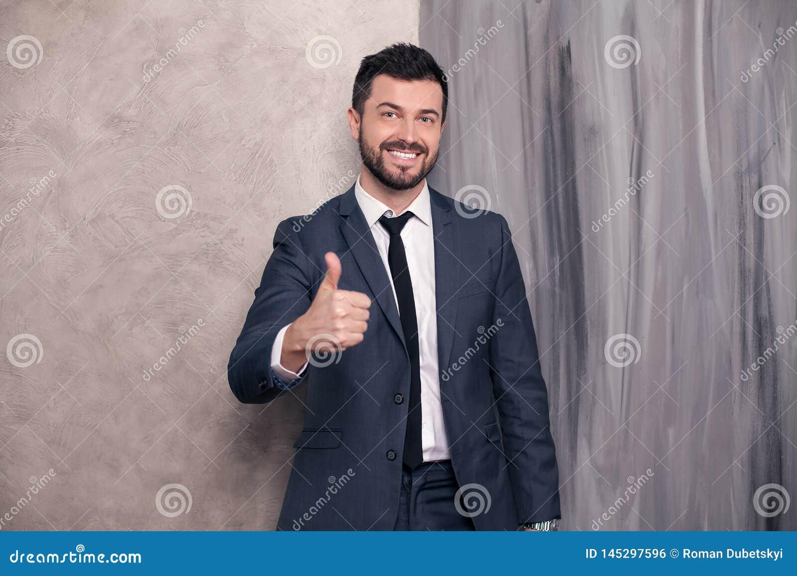 Il bello uomo d affari felice bello sta stando nel suo ufficio che mostra il sospiro e sorridere freschi vestito d uso e un legam