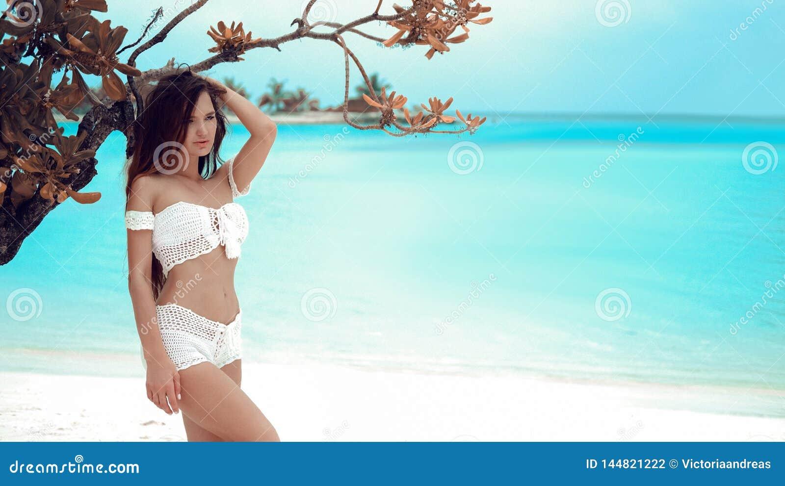 Il bianco d uso della bella ragazza sexy lavora all uncinetto lo swimwear del bikini che posa dall albero sulla laguna dell ocean