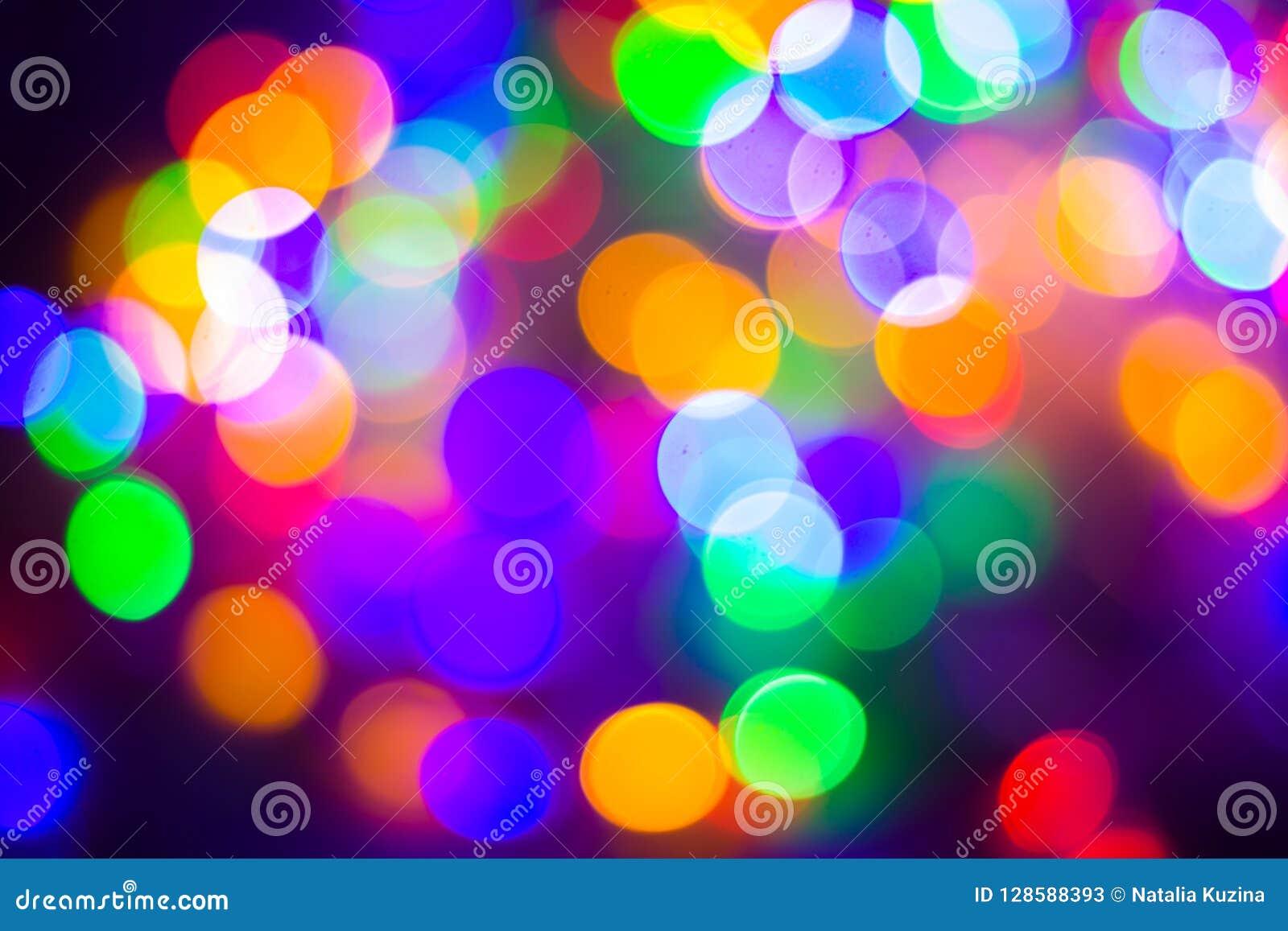 Il bokeh multicolore astratto Defocused accende il fondo Colori blu, porpora, verdi, arancio - concetto del nuovo anno e di natal
