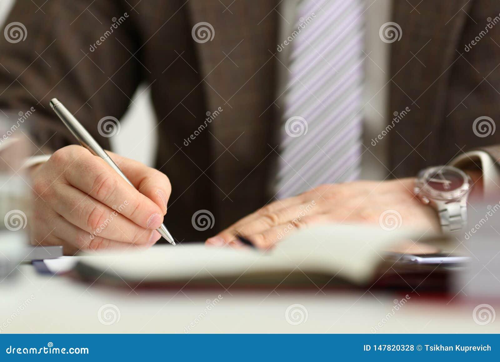 Il braccio maschio in vestito ed il legame tengono la penna d argento