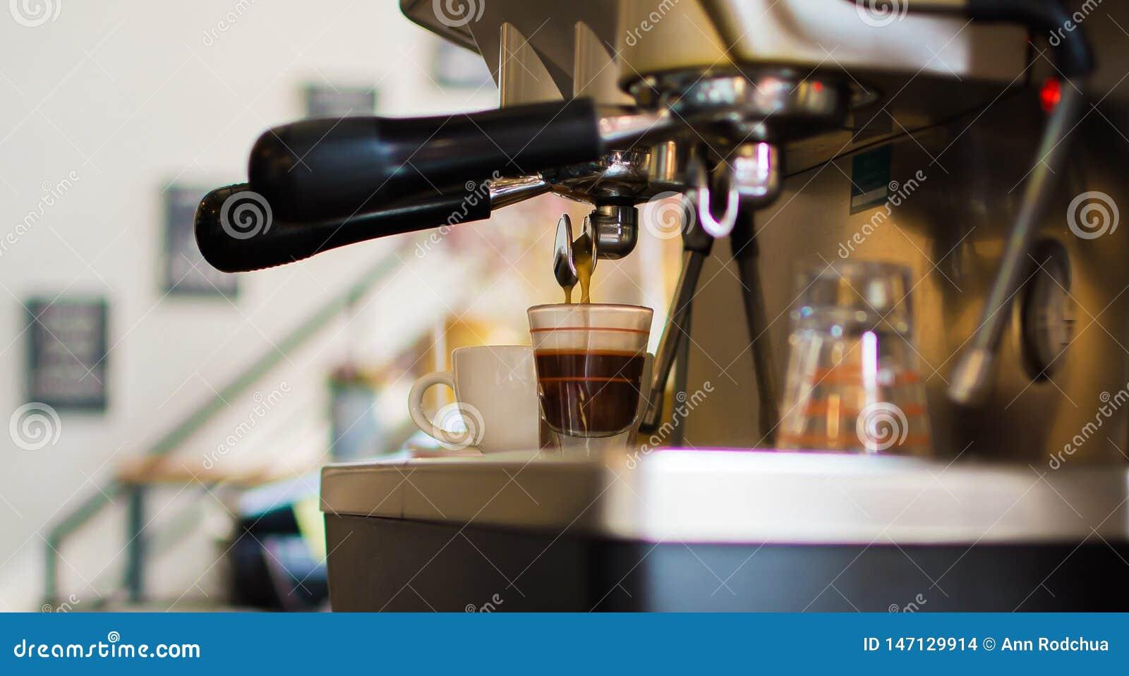 Il caffè sta preparando dalla macchina per servire ad un cliente