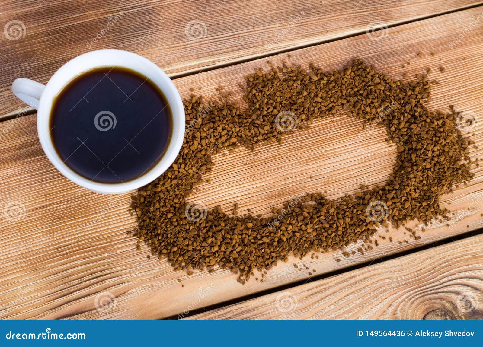 Il caff? sta accanto ad una tazza bianca riempita di caff? caldo fra i chicchi di caff? sparsi, tavola, vista superiore, orizzont
